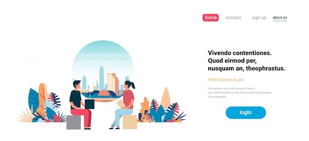 Homme femme couple à l'aide d'un ordinateur portable communiquant sur la ville gratte-ciel vue paysage urbain fond skyline flat horizontal copie espace