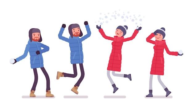 Homme et femme en doudoune s'amusant en plein air, portant des vêtements d'hiver doux et chauds, des bottes de neige classiques et un chapeau