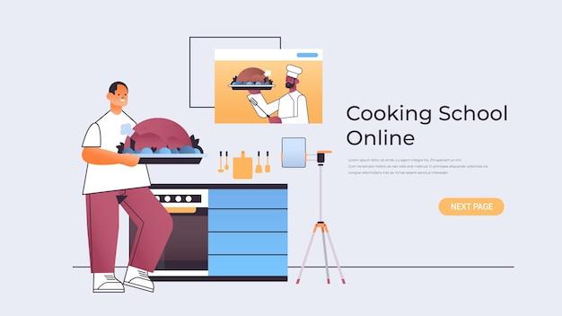 Homme food blogger préparer la dinde et regarder le didacticiel vidéo avec chef afro-américain dans la fenêtre du navigateur web école de cuisine en ligne concept copie horizontale illustration de l'espace