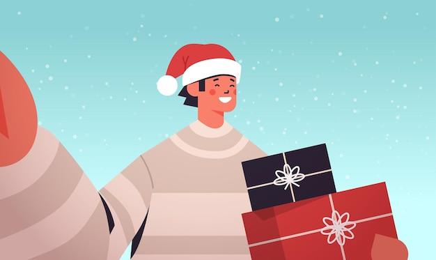 Homme heureux en bonnet de noel tenant la caméra et prenant selfie guy avec des cadeaux célébrant le nouvel an vacances de noël illustration vectorielle portrait horizontal