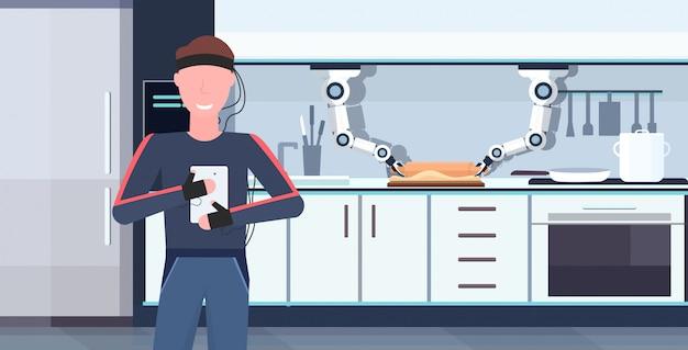Homme humanoïde avec des fils électrodes indicateurs à l'aide d'une application mobile contrôlant le robot de poche intelligent intelligent assistant robotique innovation concept d'intelligence artificielle intérieur de cuisine moderne horizontal