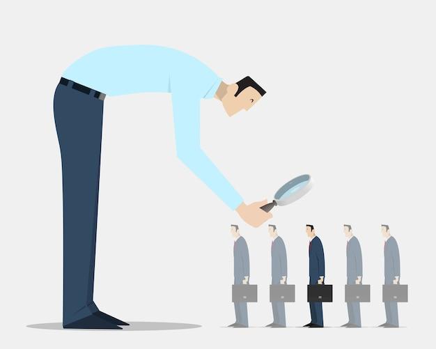 Homme avec loupe en choisissant la bonne personne parmi un groupe de boursiers identiques