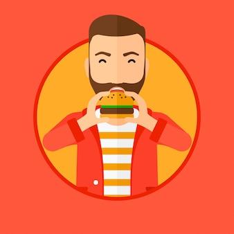 Homme mangeant un hamburger.