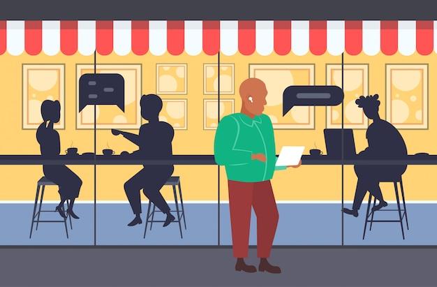 Homme marchant en plein air à l'aide de l'application mobile chat bulle communication discours conversation concept personnes silhouettes assis à table boire du café moderne rue café extérieur pleine longueur