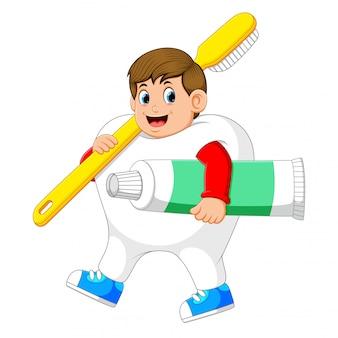 Un homme marchant et portant un costume de dent portant une grosse brosse à dents et un gros dentifrice