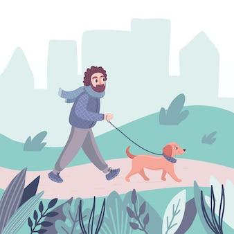 Un homme marche avec un chien teckel dans le parc