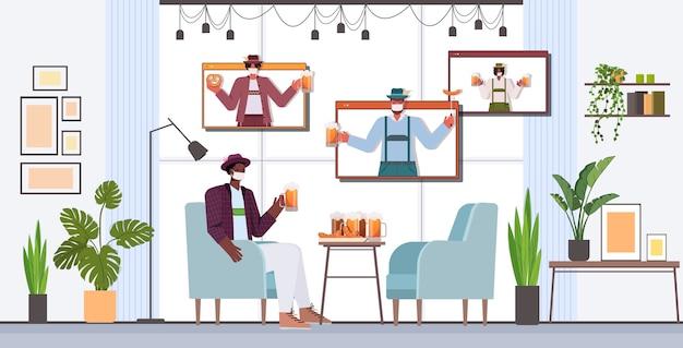 Homme en masque buvant de la bière discuter avec des amis lors d'un appel vidéo