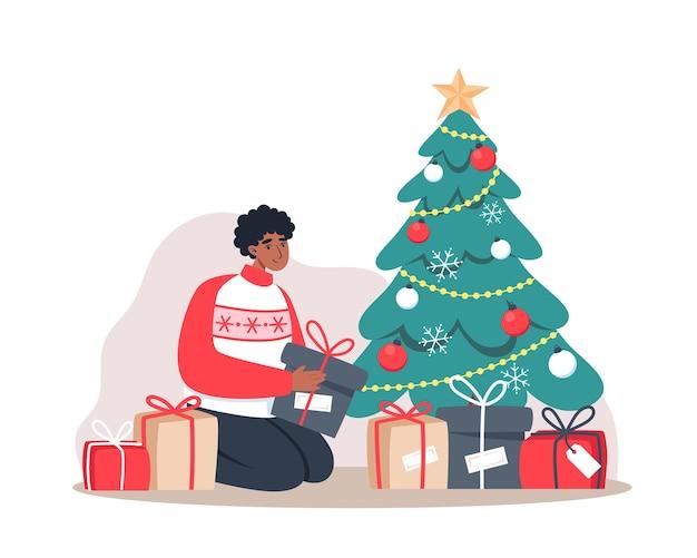 L'homme met des cadeaux sous l'arbre de noël