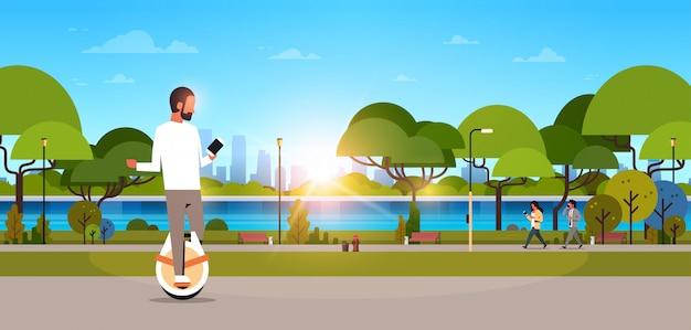 Homme monter mono roue électrique à l'aide de smartphone