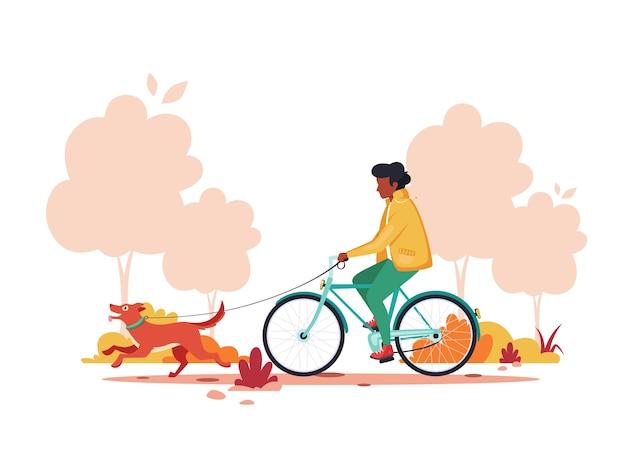 Homme noir à vélo avec chien dans le parc de l'automne. concept d'activité de plein air.