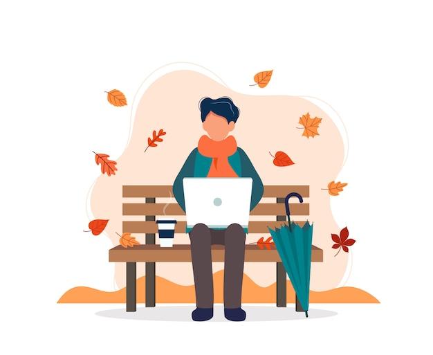 Homme avec ordinateur portable assis sur un banc en automne.