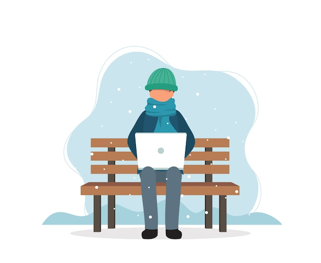 Homme avec ordinateur portable assis sur un banc en hiver.