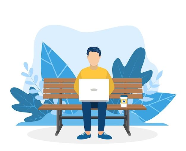 Homme avec ordinateur portable assis dans la nature