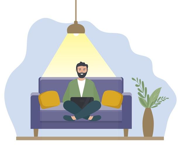 L'homme avec un ordinateur portable est assis à la maison sur le canapé