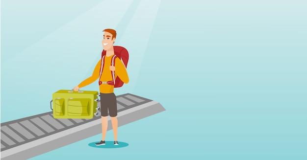 Homme ramassant la valise du tapis roulant.