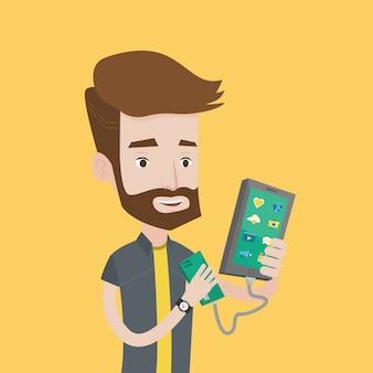 Homme rechargeant un smartphone à partir d'une batterie portable.