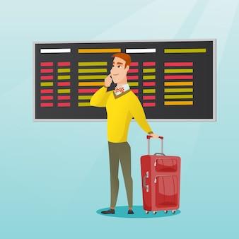 Homme regardant le panneau de départ à l'aéroport.