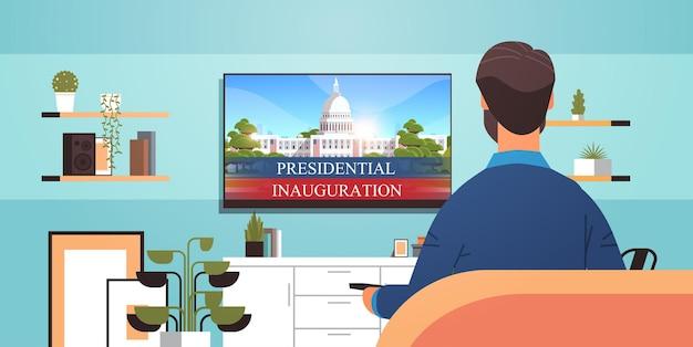 Homme regardant la télévision avec le bâtiment de la maison blanche capitol usa inauguration présidentielle jour célébration concept salon intérieur illustration vectorielle portrait horizontal