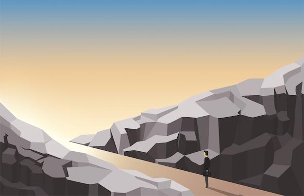 L'homme regarde devant, debout entre les rochers. la motivation commerciale, l'atteinte de nouveaux objectifs, un regard sur les perspectives d'avenir.