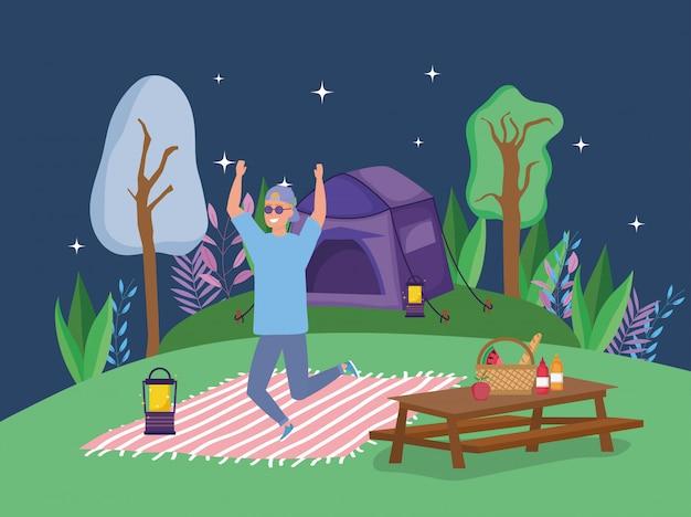 Homme sautant, lunettes soleil, lanterne, couverture, table, camping, pique-nique