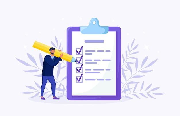 L'homme se tient près d'une grande liste de tâches et remplit la case à cocher. plan accompli, tâche accomplie. planification mensuelle, gestion du temps. liste de contrôle quotidienne