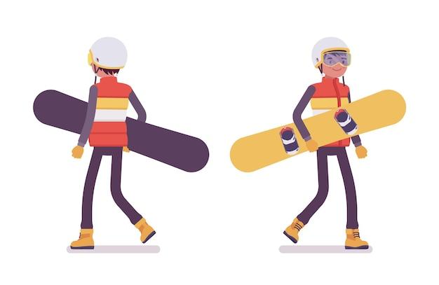 Homme sportif transportant du matériel de snowboard