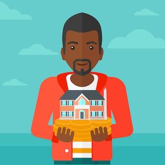 Homme tenant la maison modèle.