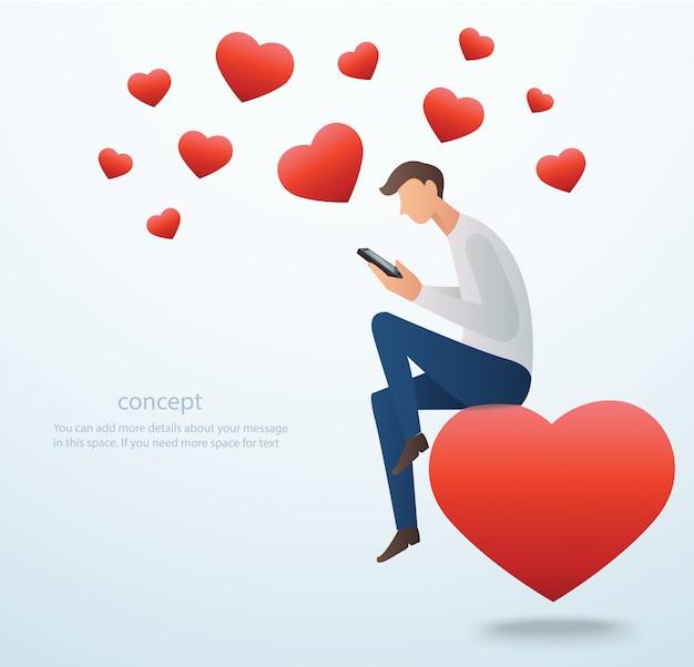 Homme tenant smartphone assis sur le coeur rouge