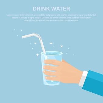 L'homme tient le verre avec de l'eau propre et de la paille à la main