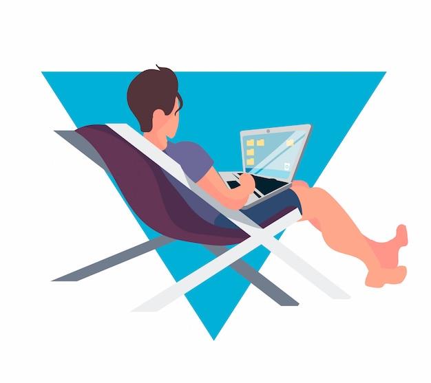 Un homme travaille sur un ordinateur portable dans un transat.