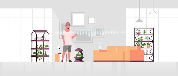 Homme utilisant un système d'arrosage automatique contrôlé par un haut-parleur intelligent