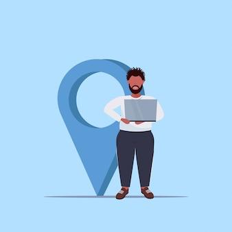 Homme, utilisation, géo, étiquette, pointeur, américain africain, type, tenue, ordinateur portable, près, emplacement, marqueur, gps, navigation, concept, pleine longueur