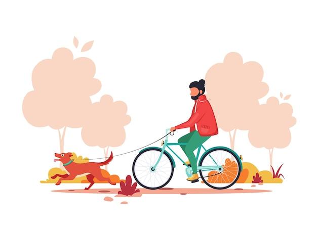 Homme à vélo avec chien en automne parc. concept d'activité de plein air.