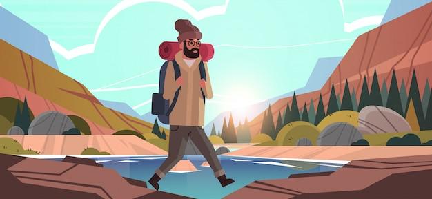 Homme voyageur randonnée avec sac à dos voyage style de vie wanderlust aventure concept guy randonneur marche en plein air montagnes rocheuses coucher de soleil paysage fond horizontal