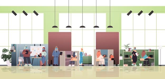 Hommes d & # 39; affaires arabes dans des masques discutant lors de la réunion dans le concept de pandémie de coronavirus du centre de coworking créatif