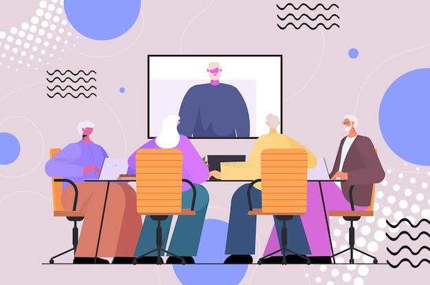 Hommes d'affaires seniors ayant une conférence en ligne rencontrant des hommes d'affaires discutant avec un leader lors d'un appel vidéo