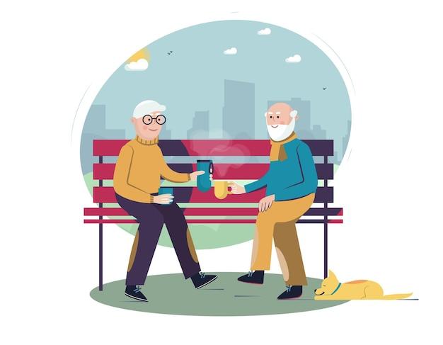 Hommes âgés assis sur le banc et buvant du thé ou du café dans une bouteille thermos