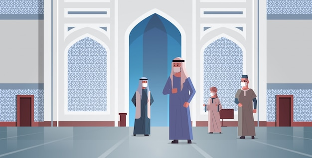 Les hommes arabes dans des masques médicaux venant à la construction de la mosquée nabawi pandémie de quarantaine de quarantaine