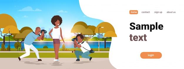 Les hommes professionnels photographes à l'aide de caméra tir femme sous différents angles modèle fille posant parc urbain paysage fond horizontal pleine longueur copie espace