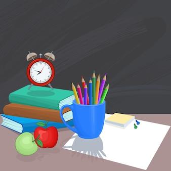 Horloge sur livre avec crayon de couleur et pomme.