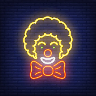 Icône de sourire clown néon. artiste de cirque avec grand arc sur fond de mur de brique sombre.