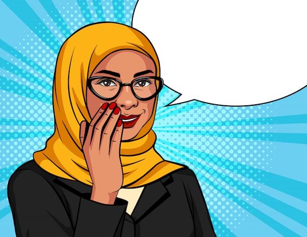 Illustration couleur dans un style pop art. la femme musulmane dans une écharpe et des lunettes traditionnelles chuchote. femme d'affaires réussie arabe sur fond de points dit une information secrète