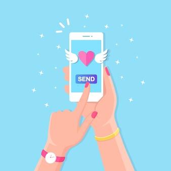 Illustration de la saint-valentin. envoyez ou recevez des sms d'amour, des lettres, des e-mails avec un téléphone mobile. téléphone portable blanc en main sur fond. voler le coeur rouge avec des ailes.