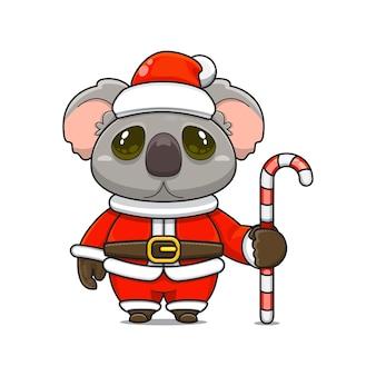 Illustration vectorielle de mascotte koala monstre mignon portant un costume de père noël tenant une canne en bonbon