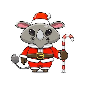 Illustration vectorielle de mascotte de rhinocéros monstre mignon portant un costume de père noël tenant une canne en bonbon