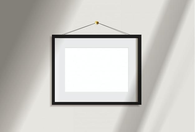 Image de cadre noir paysage vide minimal accroché sur un mur blanc avec la lumière et l'ombre de la fenêtre. isoler l'illustration.