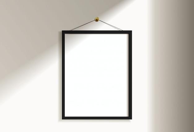 Image de cadre noir vertical vide minimal accroché sur un mur blanc avec la lumière et l'ombre de la fenêtre. isoler l'illustration.