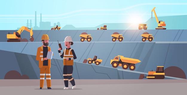 Ingénieurs utilisant des travailleurs de la radio et de la tablette contrôlant l'équipement professionnel