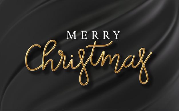 Inscription dorée réaliste joyeux noël sur fond de soie noire. texte métallique doré noël pour la conception de bannières. modèle à partir de tissu texturé et de papier d'aluminium.