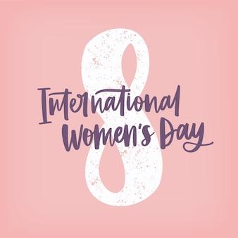 Inscription à la main de la journée internationale de la femme contre le chiffre huit sur rose